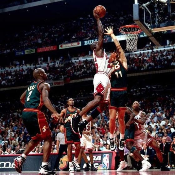 Michael Jordan of the Bulls, wearing the Jordan XI 'Playoff' dunking over Detlef Schrempf of the Sonics, wearing the Adidas EQT BB image via Getty