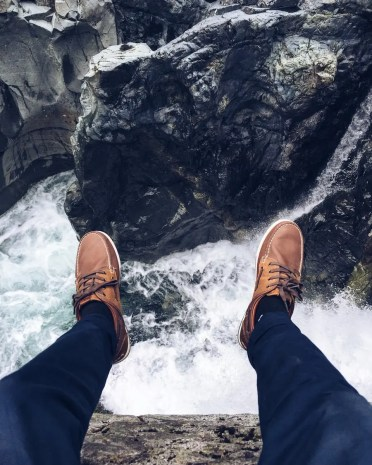 legs hanging over cliff