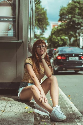 girl sitting on curb wearing shoes