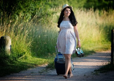 woman walking barefoot with suitcase