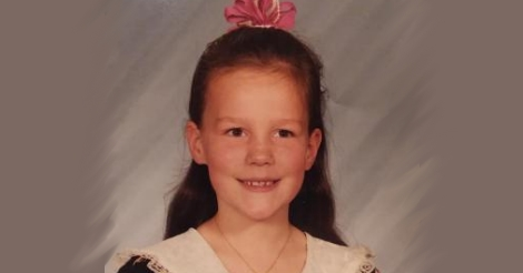 A childhood photo of Erica when she was about eight years old. She has a bow in her hair and one of those 1990s era little girl dresses.