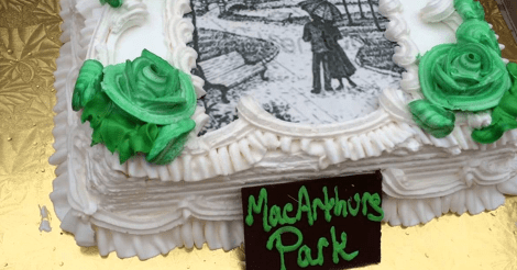 """This is a real photo from somewhere of a pretty enough white cake with green roses on it. There is also a drawing of two people in a park on it. And in front of the cake, it is labeled """"MacArthurs Park."""""""