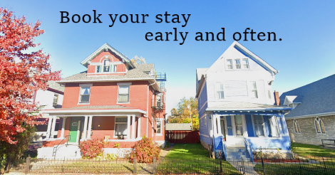 """A google street view image of the two Sneer Houses side by side: one, a handsome red brick house built in 1904. The other, a quaint yet tall blue home of narrow siding. Together, they stand upon three lots' of space.  Text on the image says """"book your stay early and often."""""""