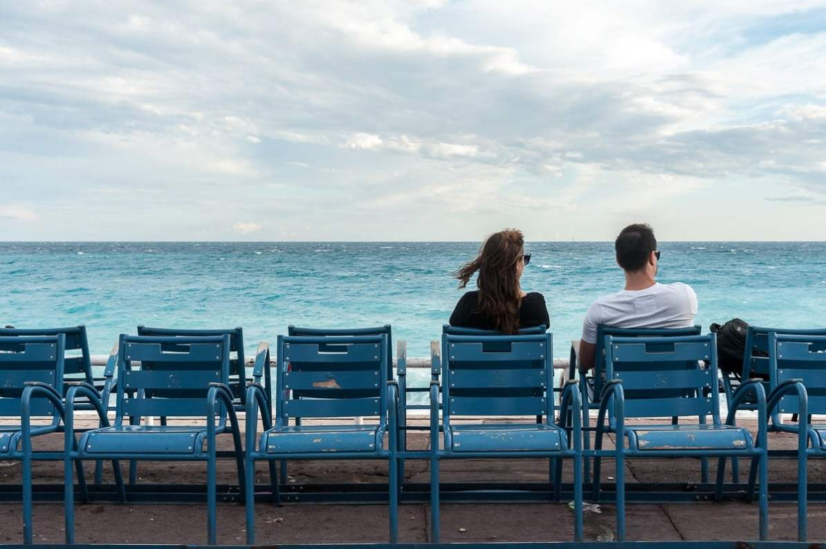 Promenade des Anglais - ein Pärchen sitzt entspannt auf blauen Stühlen und genießt den Blick auf das Wasser vor Nizza.