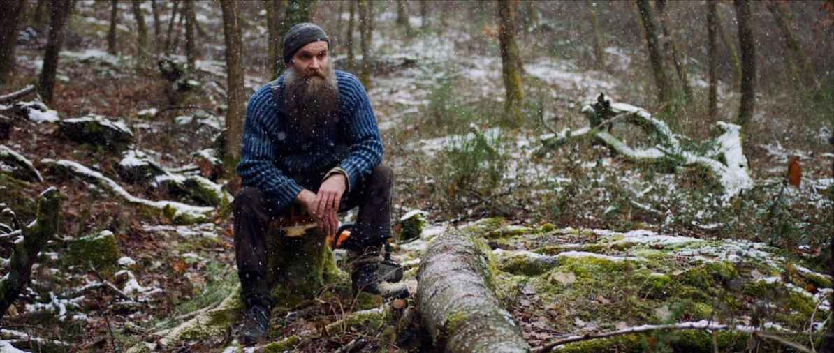 Jacques Schneider, ein Mann mit einem voluminösen Bart, eine Mütze auf dem Kopf, in seiner französischen Einöde. Er sitzt auf einem Baumstumpf im Wald, hinter ihm liegt die Kettensäge, umgefallene Baumstämm liegen am moosbewachsenen Boden, leicht ist alles mit Schnee bedeckt. Es fällt leichter Schnee.