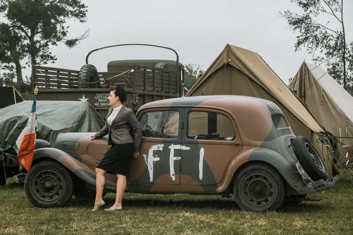 Eine Frau posiert vor einem Auto der Résistance.