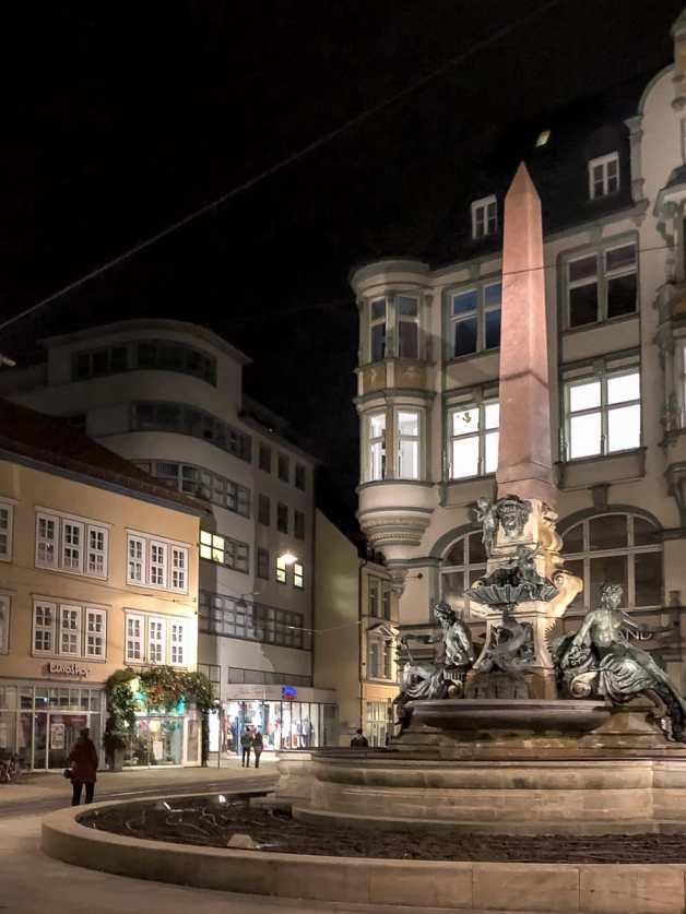 Am Angerbrunnen - Geschäftshaus Schellhorn, Neuwerkstraße 2, Erfurt im Hintergrund, bei Nacht.