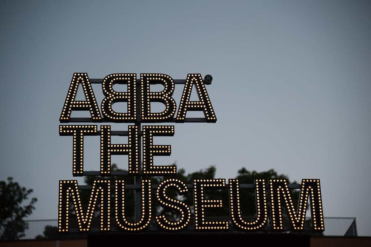 ABBA The Museum in Stockholm - Leuchtschrift am Eingang des Museums während der blauen Stunde