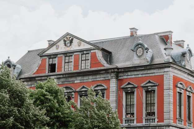 La Violette - Das Rathaus von Lüttich. Frontansicht, oberer Teil, mit etwas Grün im Vordergrund.