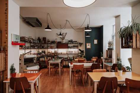 Im Inneren von Ma Ferme en Ville - Einrichtung mit Tischen, Stühlen, Regale mit lokalen Produkten.