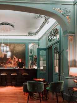 Inneneinrichtung Bar Brutàl - Barbereich mit großen Gemälden an der Wand, Stuck an der Decke, Flügeltüren, Tische und Plüschsessel