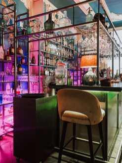 vorderer Barbereich im Industriedesign mit vielen Flaschen im Regal an der Wand