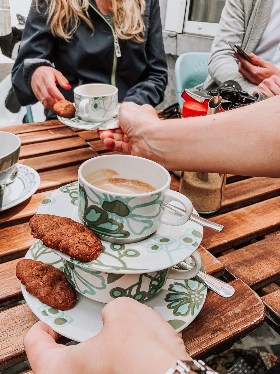 Kaffee wird gereicht - zwei Tassen mit jeweils einem Keks übereinander, während ein dritter über den Tisch gereicht wird.