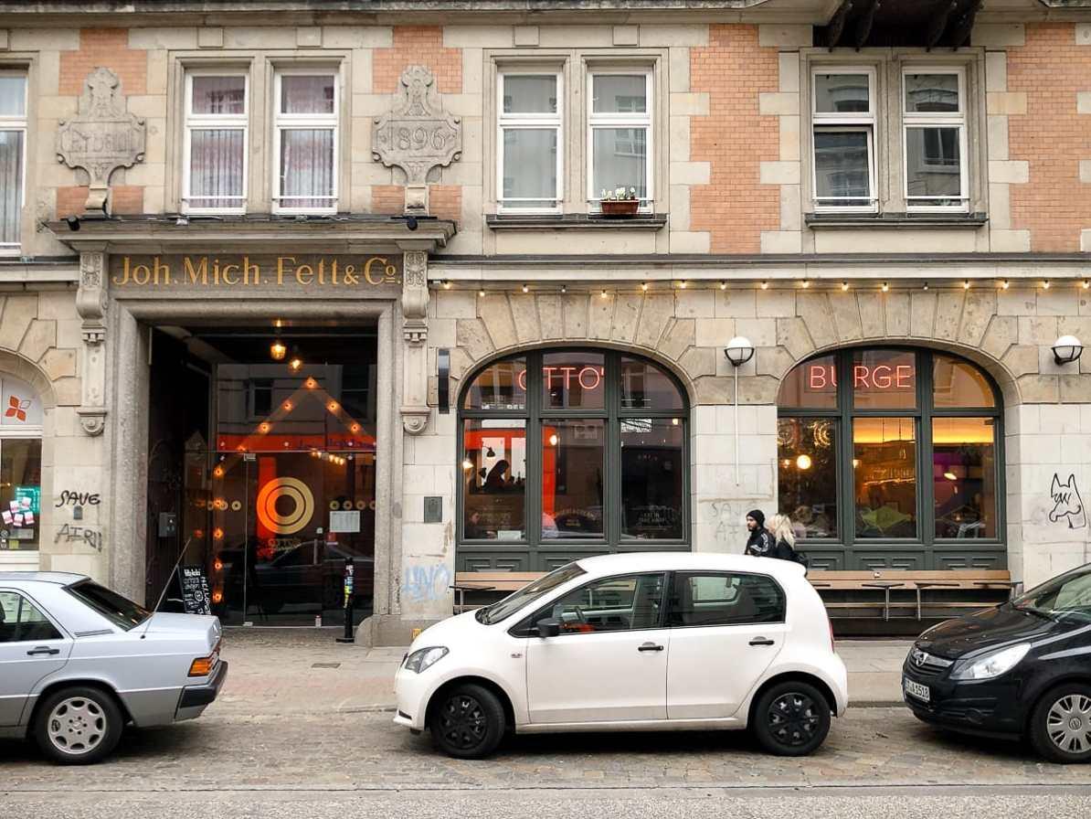 Außenansicht des Ladens in der Schanzenstraße, Hamburg von der gegenüberliegenden Seite mit parkenden Autos vor dem Laden.