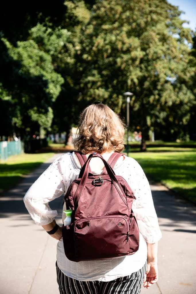 Romy Mlinzk im Westpark Dortmund unterwegs, von hinten fotografiert, pacsafe Citysafe CX auf dem Rücken.