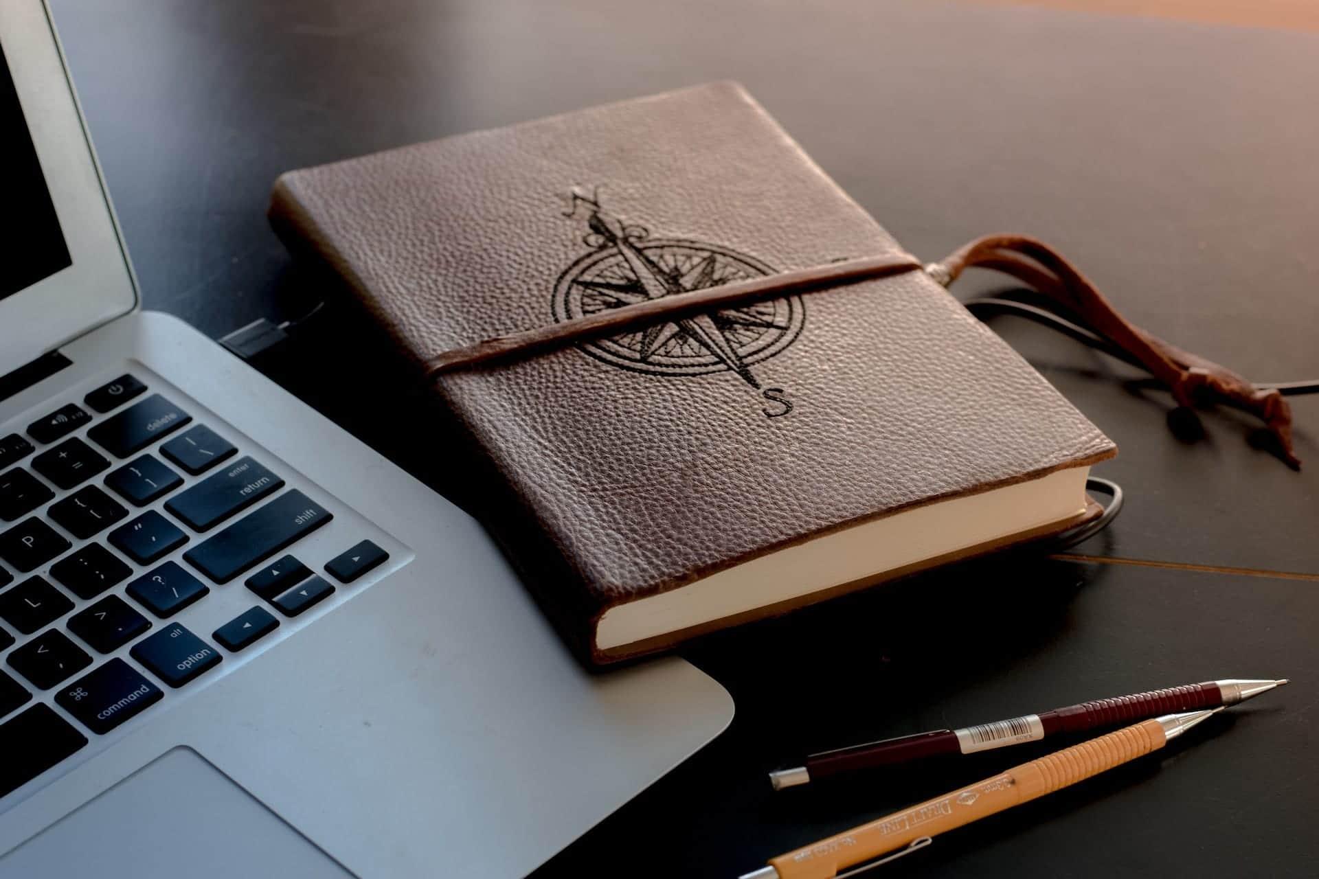 Laptop und ledernes Notizbuch mit Kompassaprägung sowie zwei Bleistiften