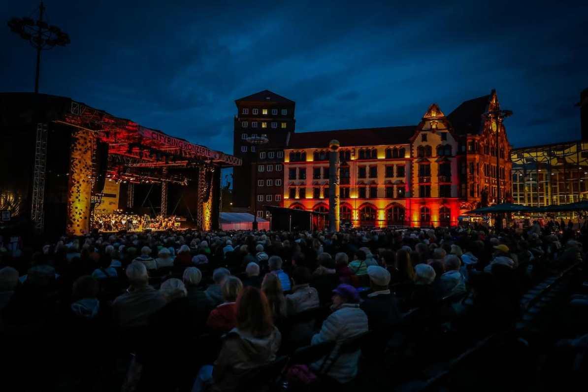 Der wunderbar bei Nacht beleuchtete Friedensplatz während der blauen Stunde. Vorne Publikum sitzend zu sehen, links die Bühne, im Hintergrund u.a. das Standesamt. Fotovermerk: Jan Heinze/Stephan Schütze