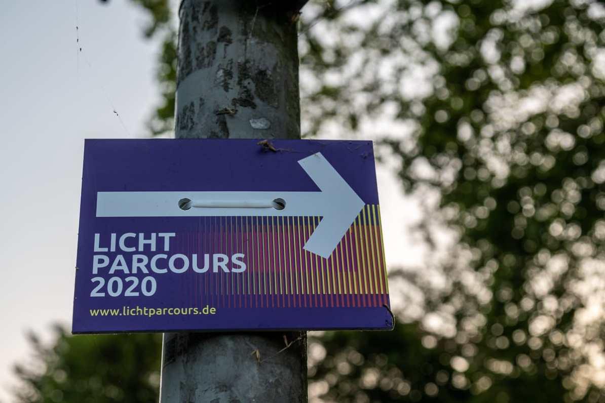 Wegweiser für den Lichtparcours 2020 inkl. Pfeil nach rechts und URL zur Website www.lichtparcours.de.