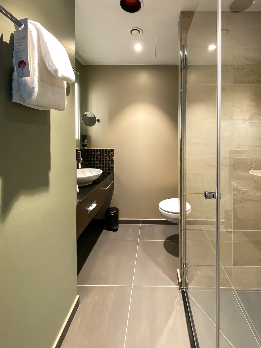 Blick ins Badezimmer eines Superior Zimmers im Leonardo Dortmund Hotel - Dusche, Toilette, dunkelbrauner Waschtisch.