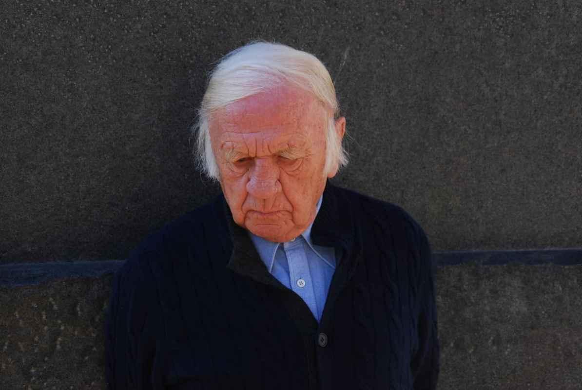 Heinz Mack, 2020 (Foto: Archiv Atelier Heinz Mack) - 90-jähriger älterer Herr mit schlohweißen Haaren mit gesenktem Blick in Hemd und Strickjacke vor einer Wand