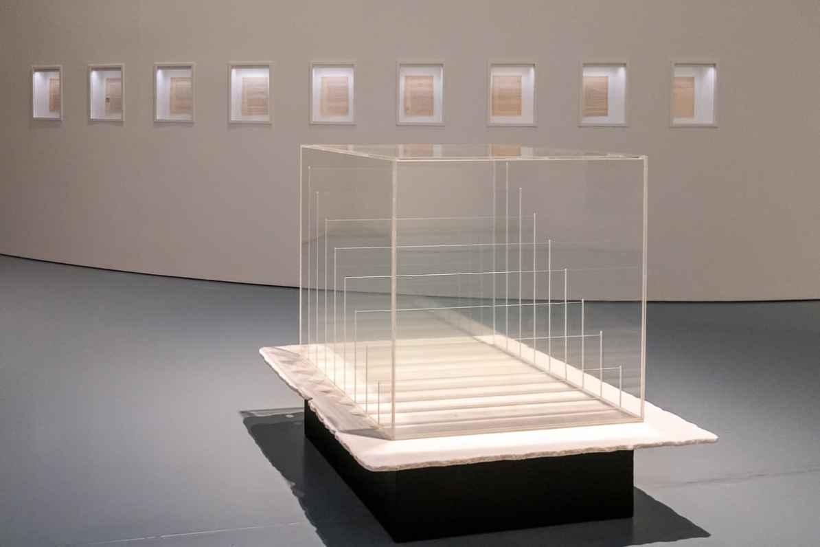 Heinz Mack - transparenter Lichtkubus und Sahara-Projekt Skript (einzelne Seiten hinter Glas an einer Wand angebracht) dahinter