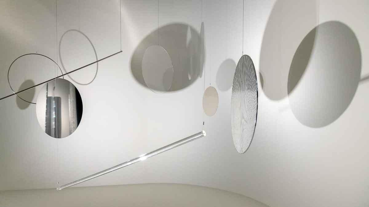 9-teilige Installation Rondo aus Kreis- und Stangenelementen, die Schatten werfen und Licht reflektieren