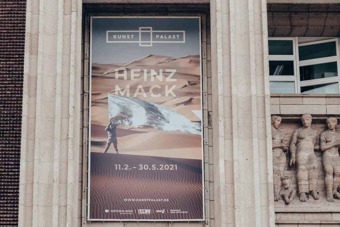 Plakat zur Ausstellung Heinz Mack, aufgehangen über dem Eingang des Kunstpalast Düsseldorf mit Daten (11.02.-30.05.2021) sowie Sponsorenlogos/Namen