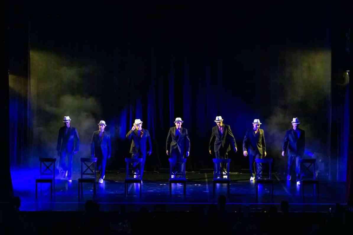 """Die sieben Akrobaten von """"Wild Boys"""" auf der Bühne des GOP Essen. Sakko offen, Hut auf, laufen jeweils auf einen Stuhl zu, unter dem Sakko oberkörperfrei."""