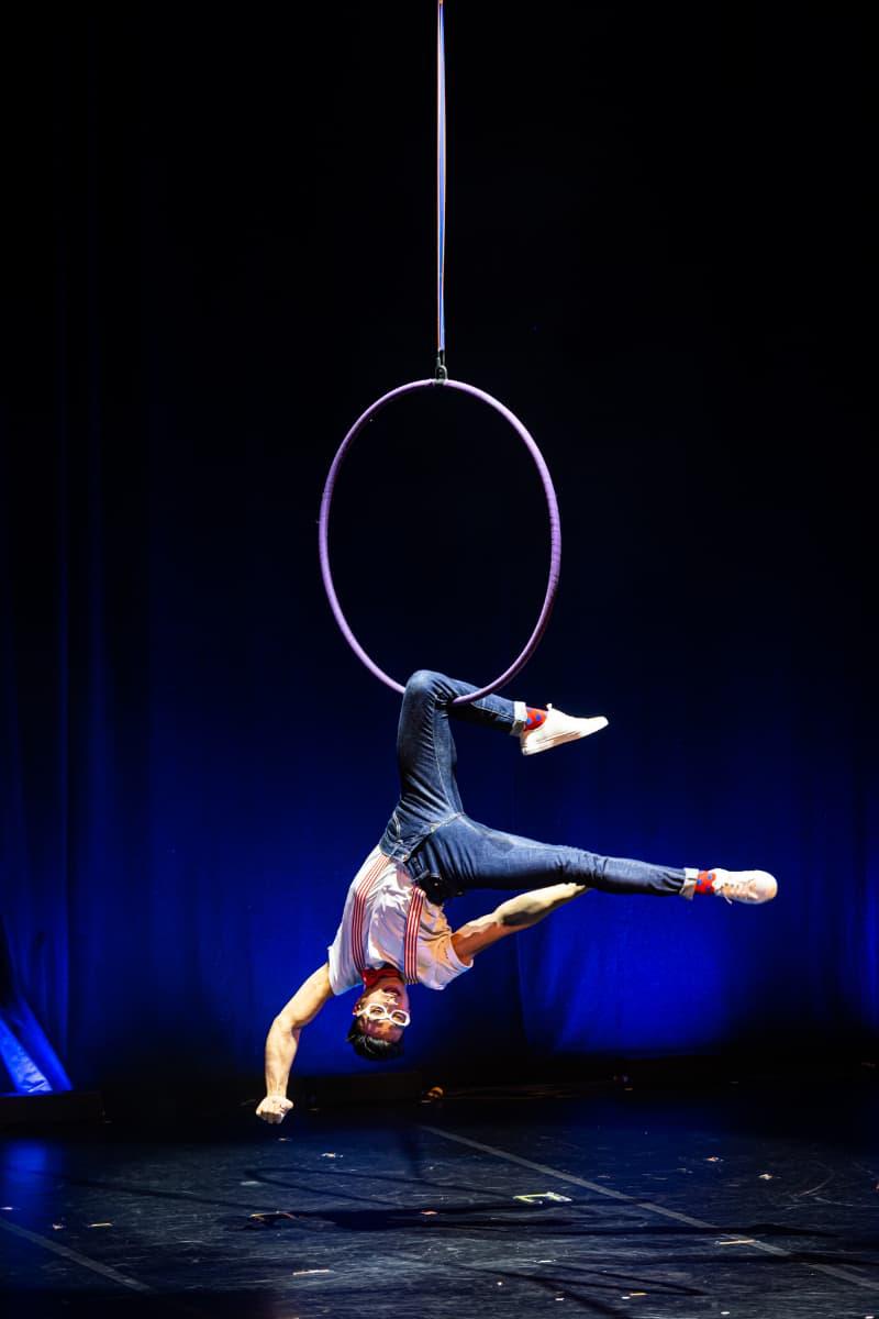 Benjamin Pring am Luftring. Er hängt kopfüber nach unten, nur am linken Knie im Ring aufgehängt.