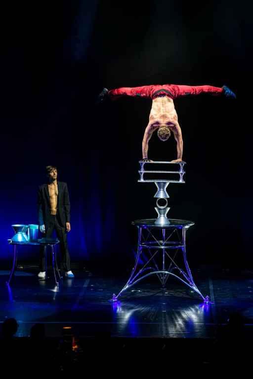Maxim Kriger mit seiner Rola Rola Akrobatik - er macht einen Handstand mit einem Spagat der Beine in der Luft auf drei Rollen und drei Brettern.