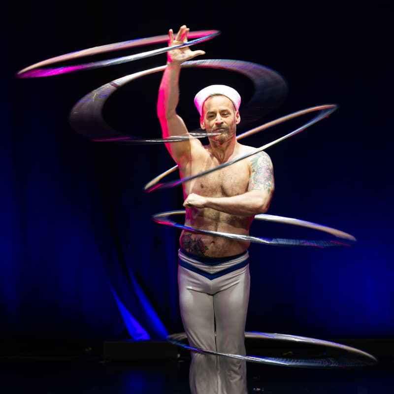 Tigris steht mit dem Gesicht zum Publikum und lässt mindestens 5 Hula Hoop Reifen um sich Kreisen, um die Knie, Oberkörper, Hals, Arm, Hand.