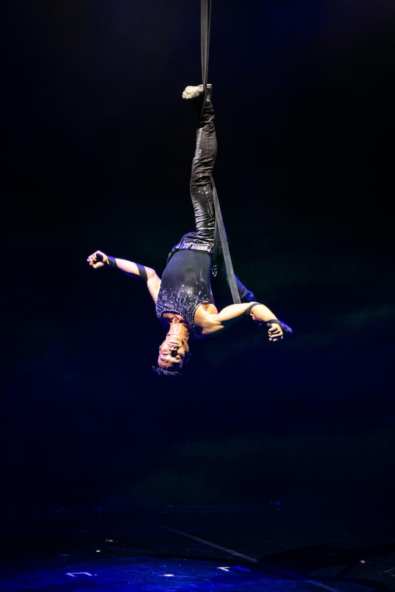 Choreograph Benjamin Pring hängt am rechten Fuß vom Band nach unten herab. Die Arme rechts und links ausgestreckt und mit Strapaten umwickelt.