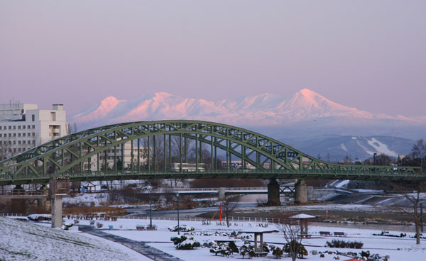 Hokkaido's highest mountains tower behind the city