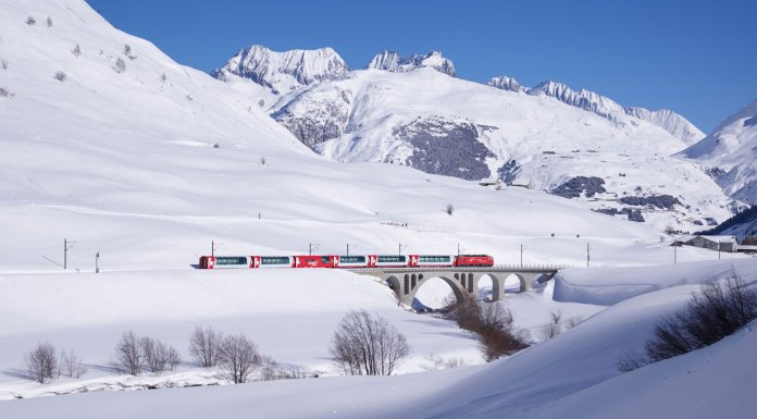 Glacier Express rolling past ski resorts in winter