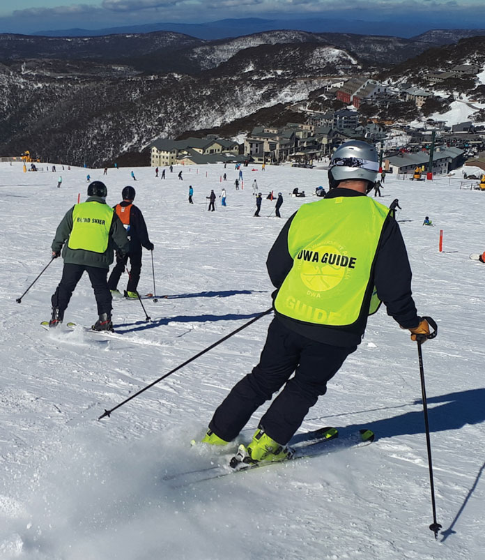 Vision impaired skier with DWA guides on the Summit at Mt Hotham