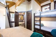 The upper loft bedroom sleeps 4 in a king and two bunks, with a private bathroom [Cedar]