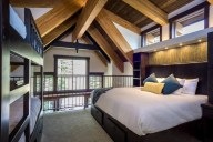 The loft bedroom sleeps four in a king and two bunks under stunning architectural details [Tamarack]