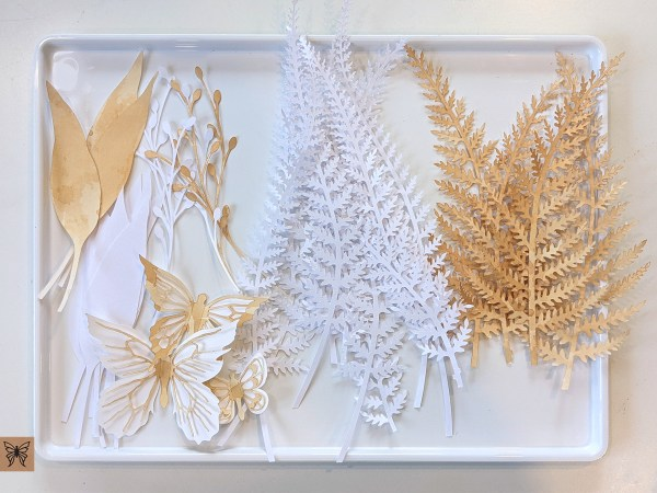 Tray of paper leaf cutouts