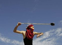 A masked Palestinian demonstrator in the West Bank village of Nabi Saleh wields a catapult against Israeli troops during clashes following a weekly protest of the Israeli settlement expansion. By Majdi Mohammed, AP Oct 28, 2011.