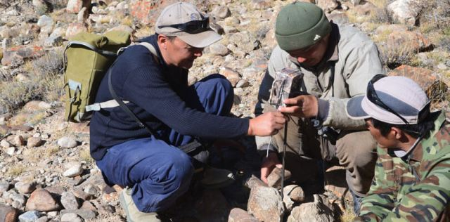 Kuban Jumabai uulu and a Kyrgyz ranger set up a camera trap to monitor snow leopards and their prey - and people who may want to harm them.