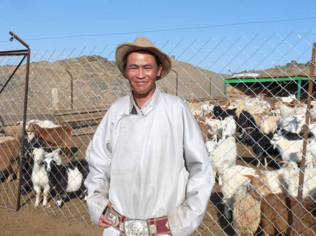 Munkhjargal stands in front of his new predator-proof corral fence, built in partnership with the Snow Leopard Trust