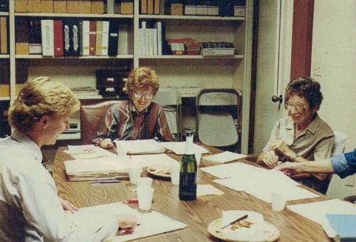 Helen sitting at a table with other women looking at documents