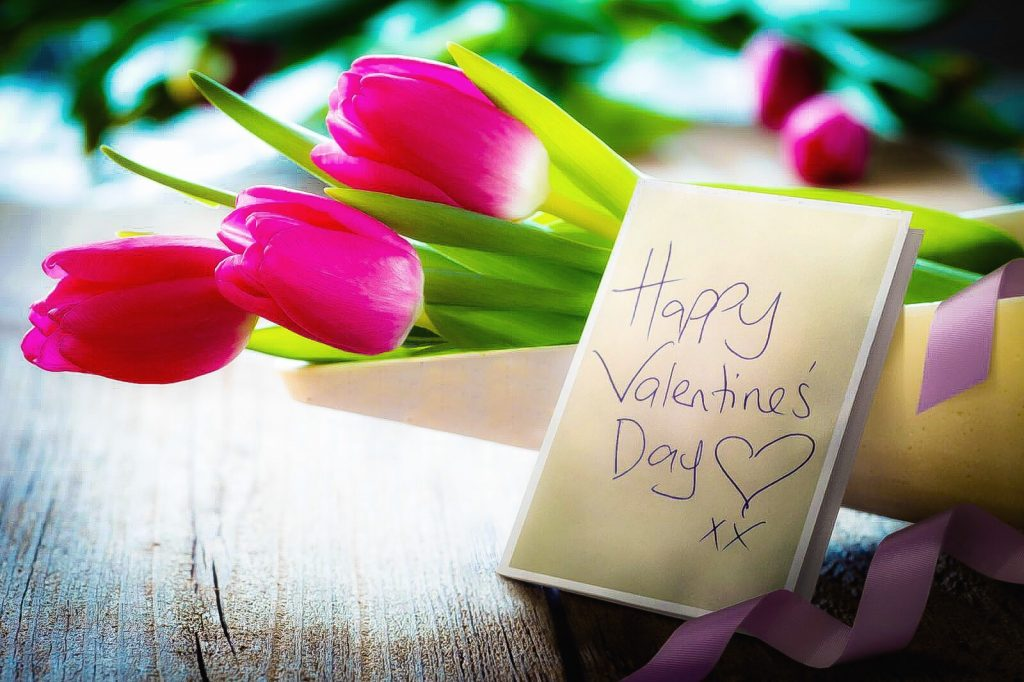 pink tulips in a vase with a letter that says happy valentines day
