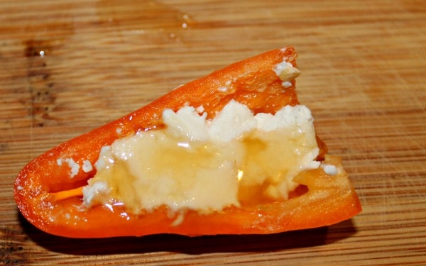 Uncooked mini pepper stuffed with goat cheese and drizzled with honey on cutting board