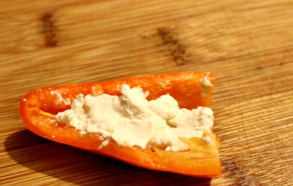 Mini pepper on wood cutting board stuffed with goat cheese