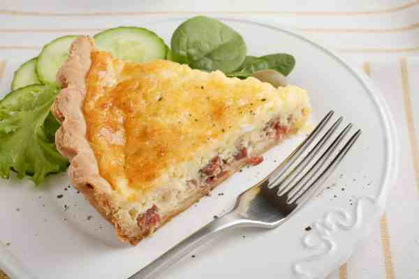 slice of bacon quiche on a white plate with a silver fork