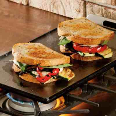 Sandwiches cooking on a plancha grill on gas oven top