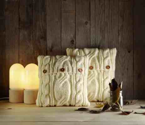 White sweater knit pillows against wooden backdrop