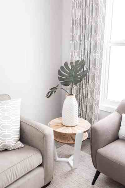 Corner of a living room with a couch, chair, and endtable. End table has a white vase with a palm tree on it.
