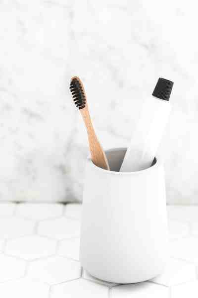 Bathroom sink with container containing toothbrush and toothpaste